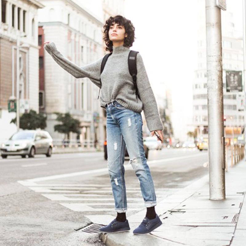 chica en la calle pidiendo taxi, lleva zapatillas army blue muroexe